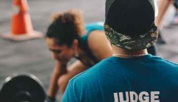 man in blue crew neck shirt staring at woman trying to lift barbell