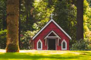 red chapel on grassy field with trees