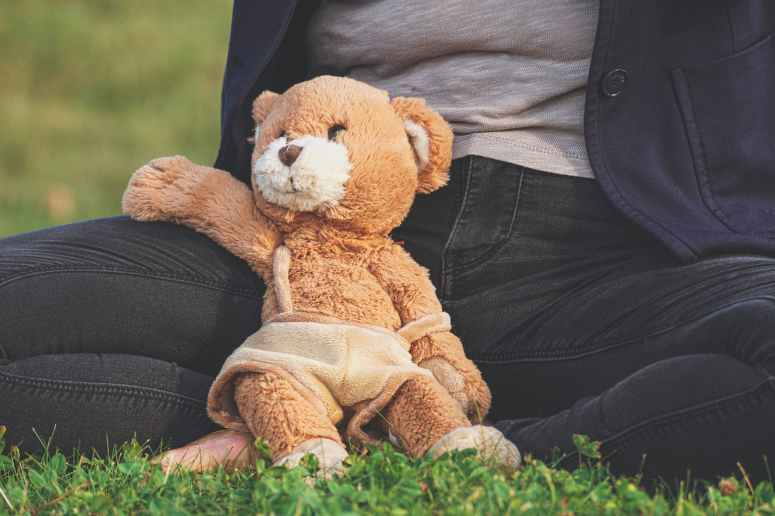 brown teddy bear toy leaning on person