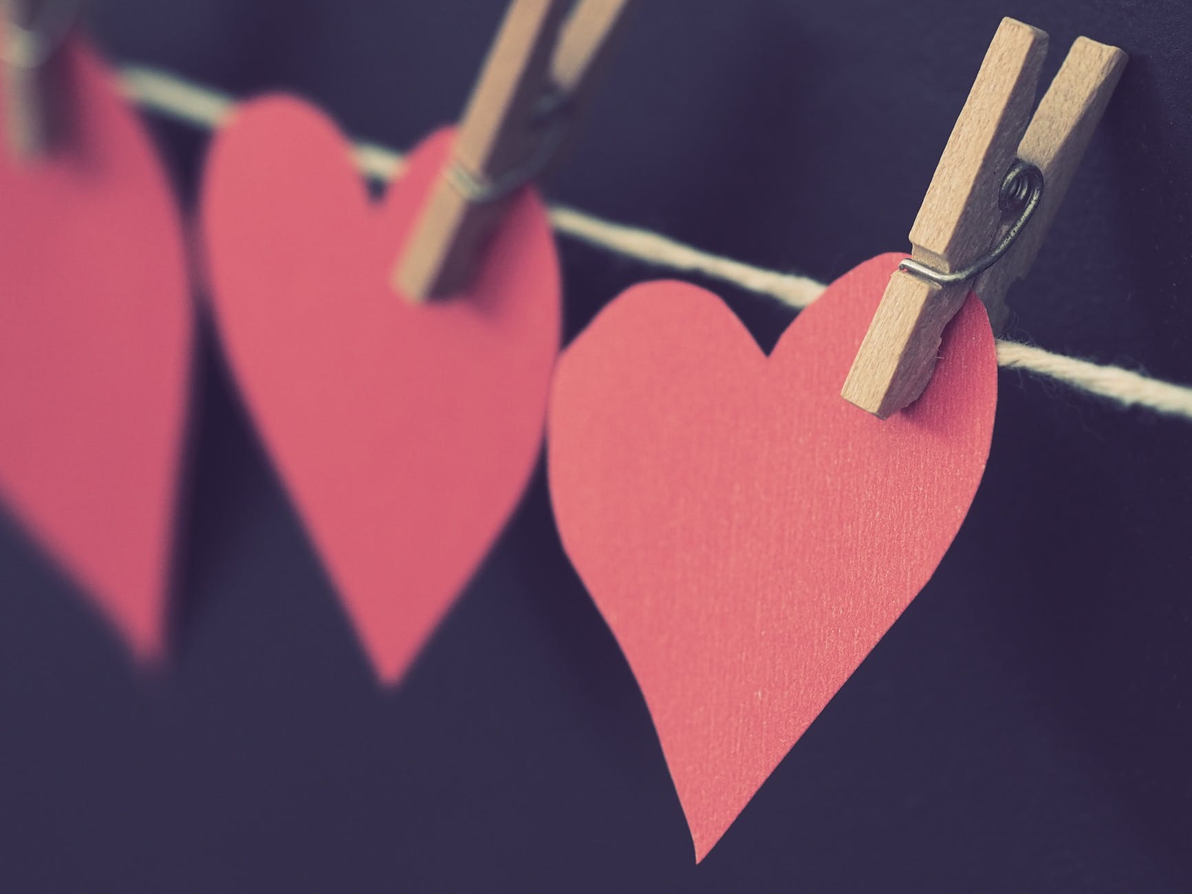 photo of red heart shaped paper hanging on rope